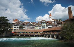 Covered bridge, church, castle and river view in Thun (Switzerland). Looking towards the covered bridge Untere Schleusenbrucke at the Muhleplatz in Thun stock photo