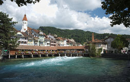Covered bridge, church, castle and river view in Thun (Switzerland). Looking towards the covered bridge Untere Schleusenbrucke at the Muhleplatz in Thun royalty free stock images