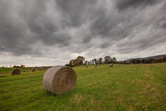 Scenic view of hay bales in a countryside field. With dark grey autumn clouds in the sky Royalty Free Stock Image