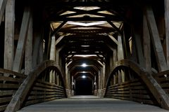 Covered Bridge at Night. A magnificent covered bridge gives reflection of light   during the nighttime hours Royalty Free Stock Photography