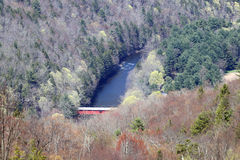 Covered bridge over the creek. A covered bridge over a creek surrounded by trees Royalty Free Stock Photo