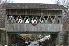 Covered Bridge over a frozen creek royalty free stock photography