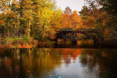 Covered bridge over river in autumn Royalty Free Stock Photography