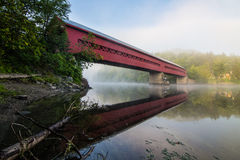 Covered bridge over river with reflection in the mist. Red covered bridge in the morning mist with reflection and green foliage Royalty Free Stock Image
