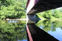 Covered Bridge Reflecting. On water in Southern Quebec royalty free stock images