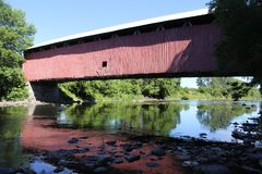 Covered Bridge Reflecting. On water in Southern Quebec royalty free stock photo