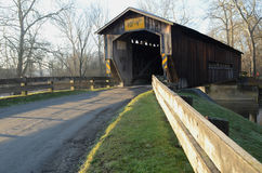 Covered bridge on rural river and woods Royalty Free Stock Photo