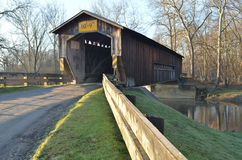 Covered bridge on rural river and woods Royalty Free Stock Image