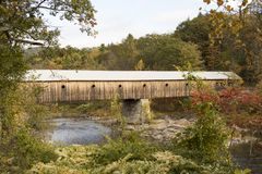 Covered bridge in rural Vermont in fall. Fall foliage on tree lined banks of river with oldest covered wooden bridge in Vermont Stock Images