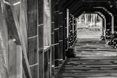 Covered Bridge with the Sun Shining in Patterns on the Wood. Black and White picture of a covered bridge with sunlight shining in patterns on the wall and floor Royalty Free Stock Photo