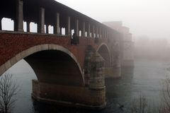 Covered bridge surrounded by fog. In winter Stock Photo