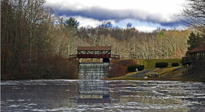Covered Bridge and Waterfall with Reflecting Lake Stock Image