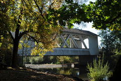 Covered Bridge. White covered bridge with shade trees and water running under it Stock Photography
