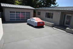 Covered car sits in driveway of modern house. Modern house with covered car in the driveway stock images