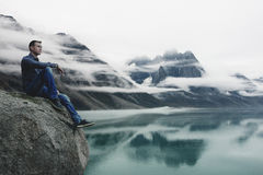 Covered with Clouds. Man Sitting on a Cliff, Watching Mountains Becoming Covered with Clouds Royalty Free Stock Photo