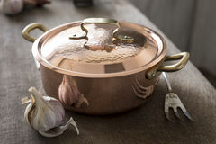 Covered Copper Cooking Pot Between Garlic and Carving Fork Stock Photography