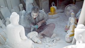 Covered by dust of marble stone carver make Buddha image in small workshop with angle-grinder Royalty Free Stock Photos