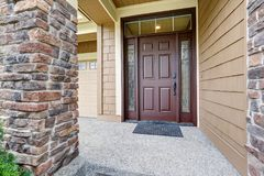 Covered entrance porch boasts front door with ornate sidelights royalty free stock photography