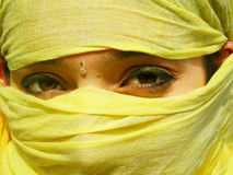 Covered Face. A face covered with yellow cloth revealing only the beautiful eyes with eyeliner and kohl on them Royalty Free Stock Photography