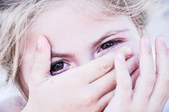 Covered face. Child covers face and is looking into the camera Royalty Free Stock Image