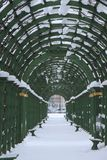A covered gallery along the alley in the park. In winter Royalty Free Stock Photo