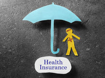 Covered by health insurance. Bandaged paper man under umbrella with Health Insurance label Stock Photos