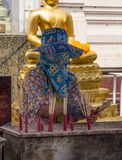 Covered lady placing candles at temple. Thai lady with mask and hat places candles in holders at a Buddhist temple in Thailand royalty free stock images
