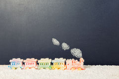 Covered locomotive train toy with smoke in snow on chalkboard ba Stock Images