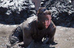 Covered in mud. A man sinks into deep mud as he participates in a dirty marathon Stock Photography