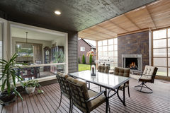Covered patio area in luxurious house. Furnished with glass top table and chairs with beige cushions, also there is fireplace and barbecue. Northwest, USA Royalty Free Stock Image