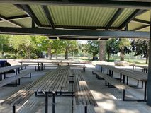 Covered picnic area with trash can and wooden picnic tables royalty free stock photography