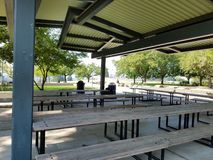 Covered picnic area with trash can and wooden picnic tables royalty free stock photos