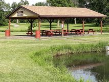 Covered Picnic Area in the Park Next to the Lake stock image