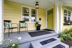 Covered porch with stairs. Small American yellow house exterior stock photography