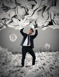 Covered by a rain of documents of bureaucracy. Businessman is repaired by a rain of big leaves Royalty Free Stock Image