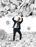 Covered by a rain of documents of bureaucracy. Businessman is repaired by a rain of big leaves Stock Images