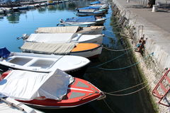 Covered small sea boats docked in a row at sea canal Royalty Free Stock Photos