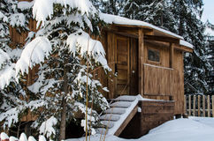 Fabulous wooden hut covered with snow in the forest. Covered with snow, a fabulous wooden hut in the forest. Carpathian Mountains, Ukraine Stock Image