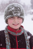 Covered with snowflakes. A close-up portrait of a ten year old boy in falling snow wearing winter clothing and snowflakes, smiling gently at the viewer Royalty Free Stock Images