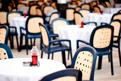 Covered with tablecloth tables for visitors to the summer outdoor cafes Stock Photos