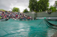Covered tennis court on rain. Tennis court covered for protection against rain. Match delayed on Roland Garros, Paris Royalty Free Stock Photography