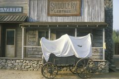Covered wagon in front of Saddlery store Stock Photo