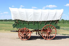 Covered Wagon. On a gravel road with tree lined grassy meadow and light blue sky in the background Stock Photography