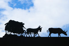 Covered wagon silhouetted with blue sky Stock Images
