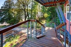 Covered walkway of amazing lake house with greenery. Covered walkway with metal railings of amazing lake house with greenery Royalty Free Stock Images