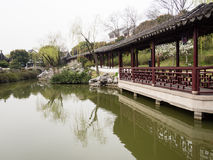 Covered walkway in classical Chinese garden with pond Royalty Free Stock Photo