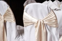 Covered wedding reception chairs with sashes royalty free stock photos