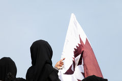Covered women and Qatar flag Stock Photos
