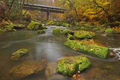 River with a covered bridge in a forest in autumn stock photo