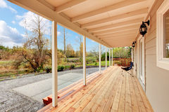 Covered wooden deck in the back yard with autumn landscape. Stock Images